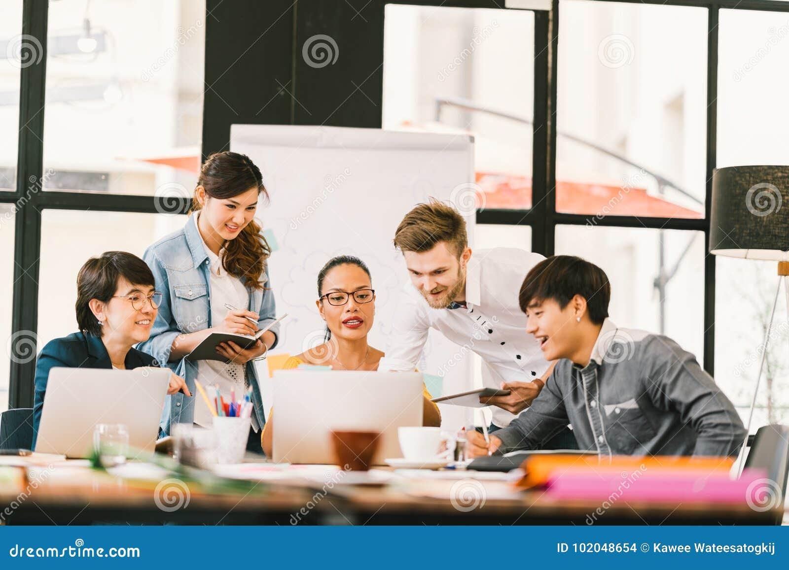 使用膝上型计算机,数字式片剂的不同种族的队讨论 工友合作,大学生会议 小企业概念