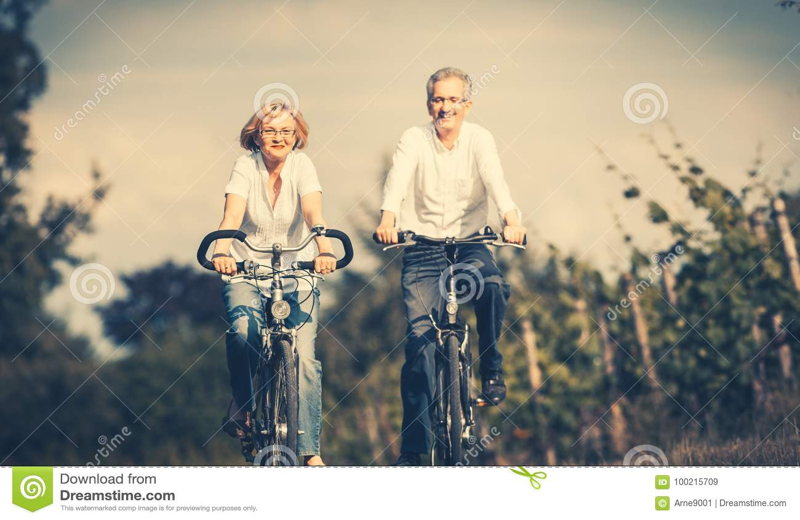 使用自行车的资深妇女和人在夏天