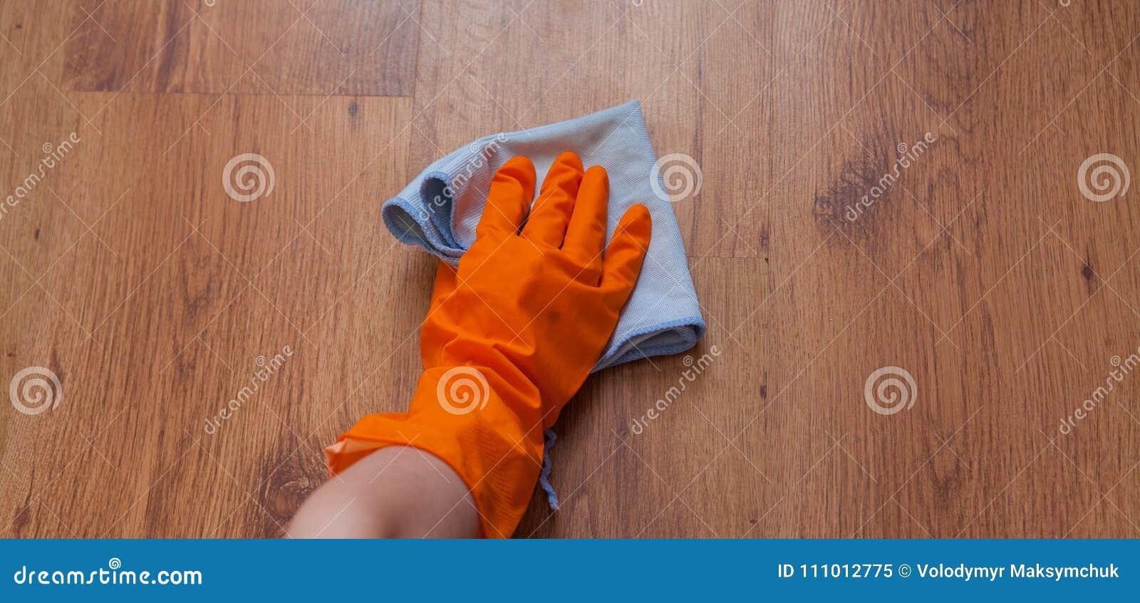 使用蓝色旧布的一只妇女手抹木地板