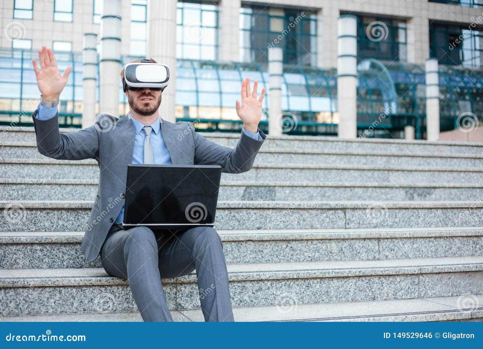 使用虚拟现实模拟器的英俊的年轻商人和做手势,运作在办公楼前面