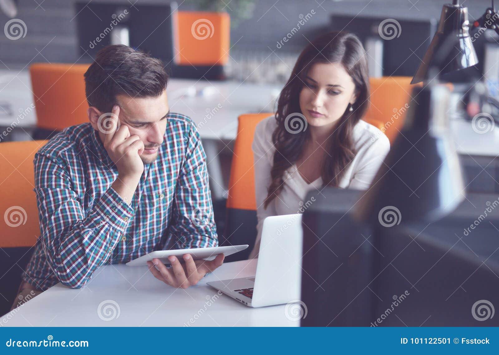 使用计算机的年轻偶然企业夫妇在办公室 Coworking,显示新的起始的想法的创造性的经理