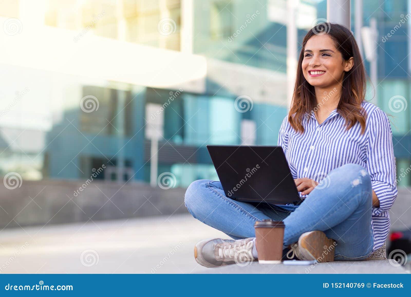 使用计算机的年轻微笑的妇女和喝咖啡户外与拷贝空间