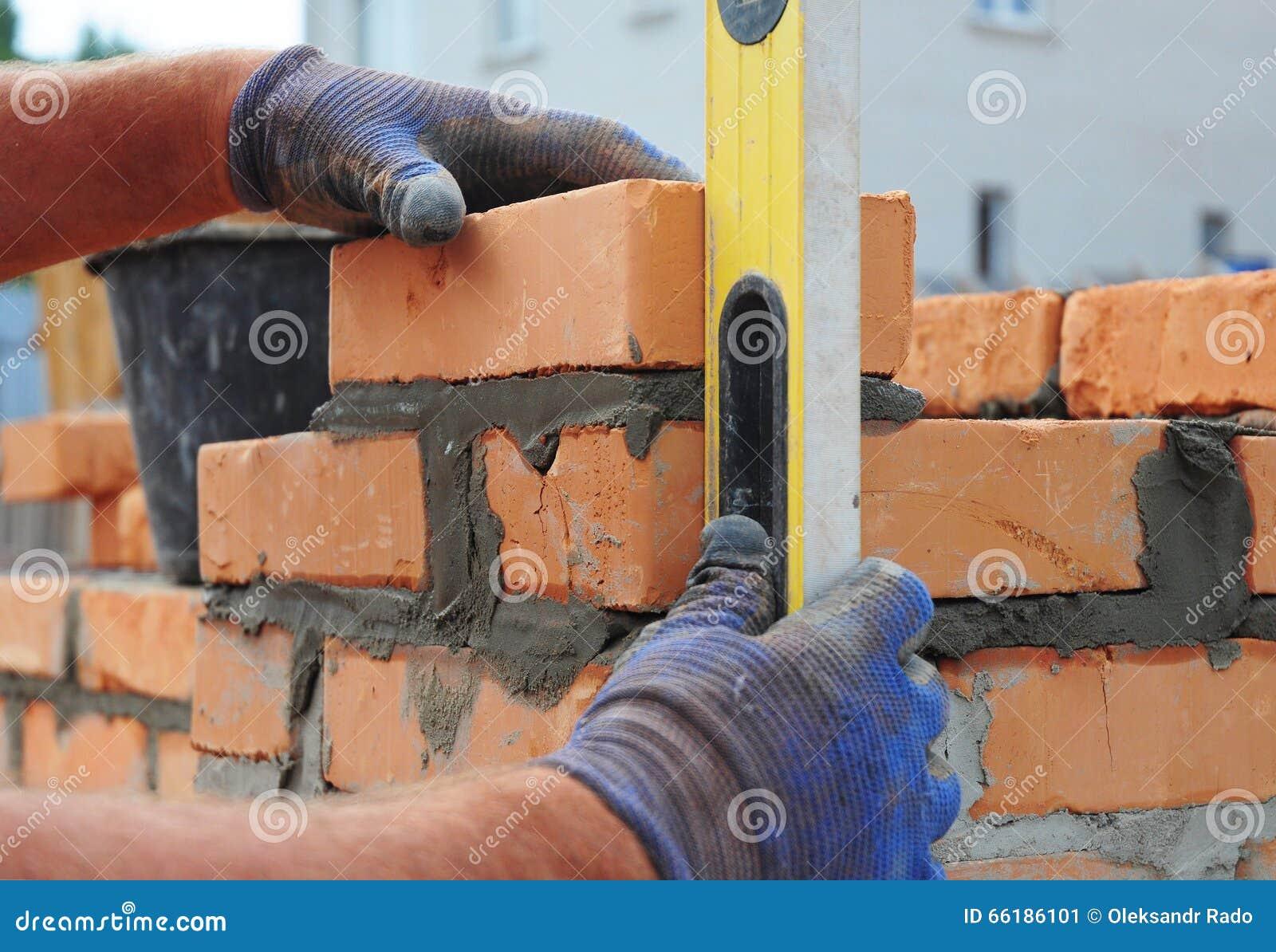 使用水平仪的瓦工检查室外新的红砖的墙壁 砌基本石工技术