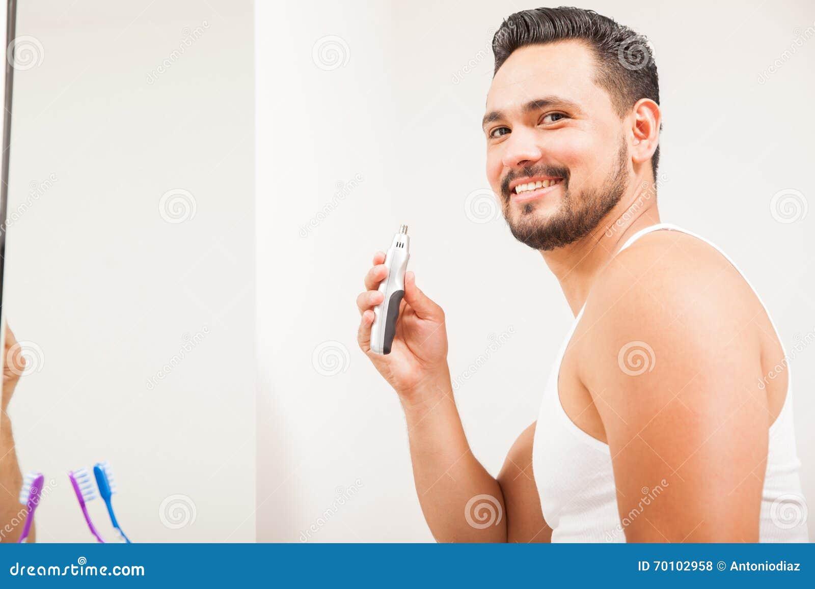 使用鼻毛整理者的年轻拉丁人