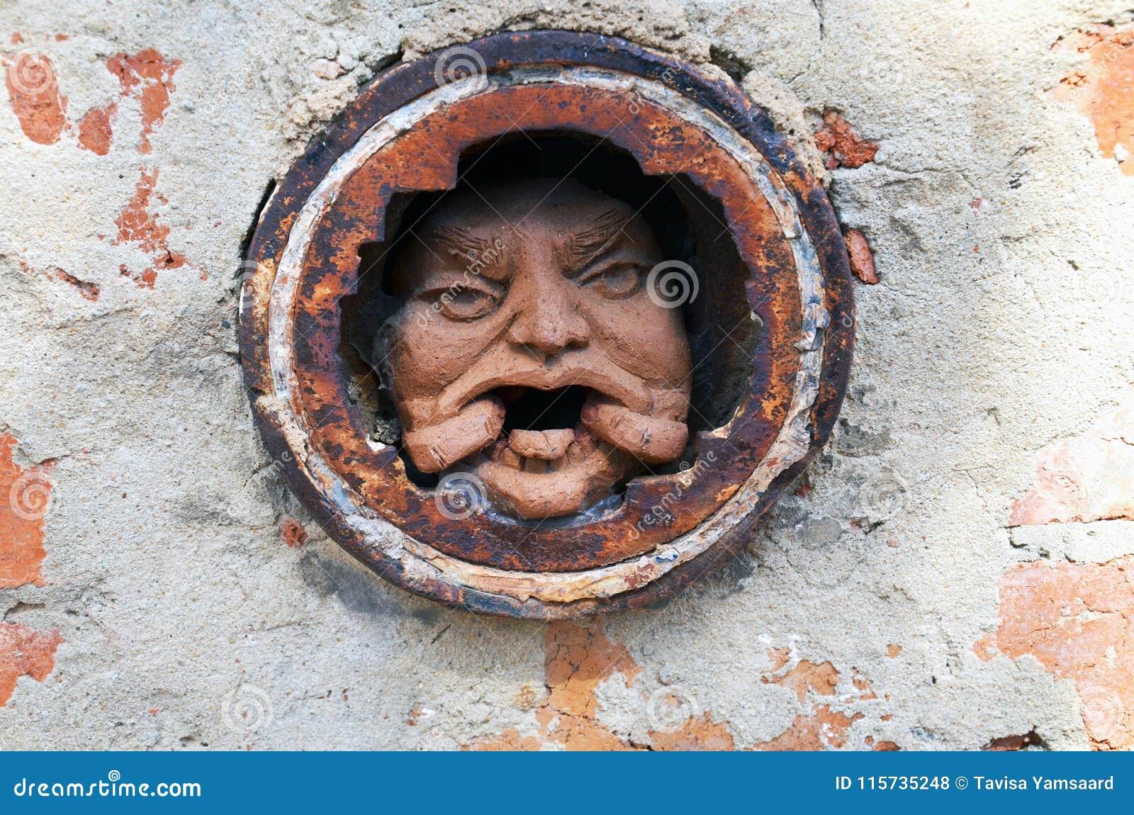供以人员在孔的` s面孔在砖墙在墨尔本