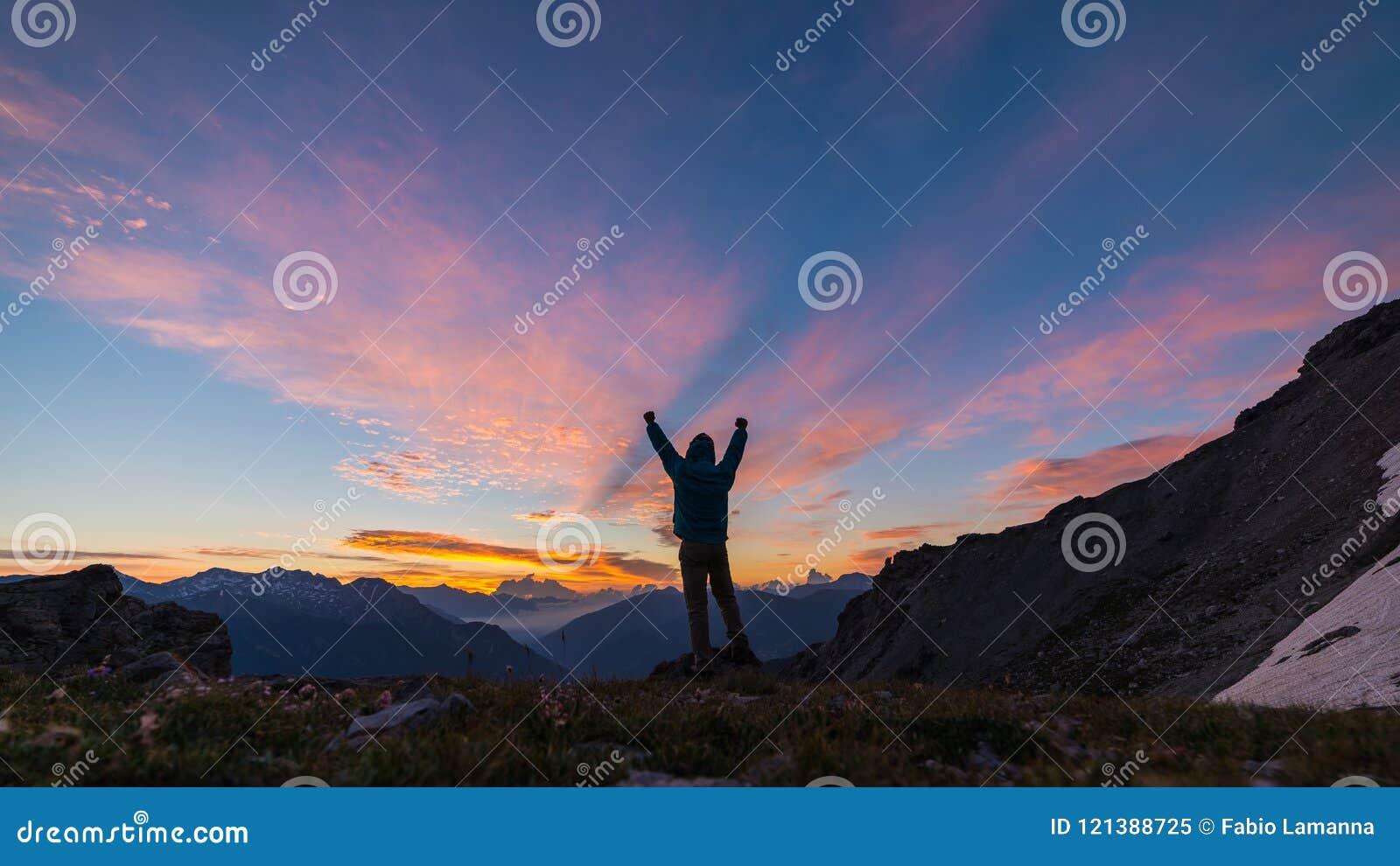 供以人员在山顶面上升的胳膊的身分,轻的五颜六色的天空scenis环境美化的日出,征服成功领导概念