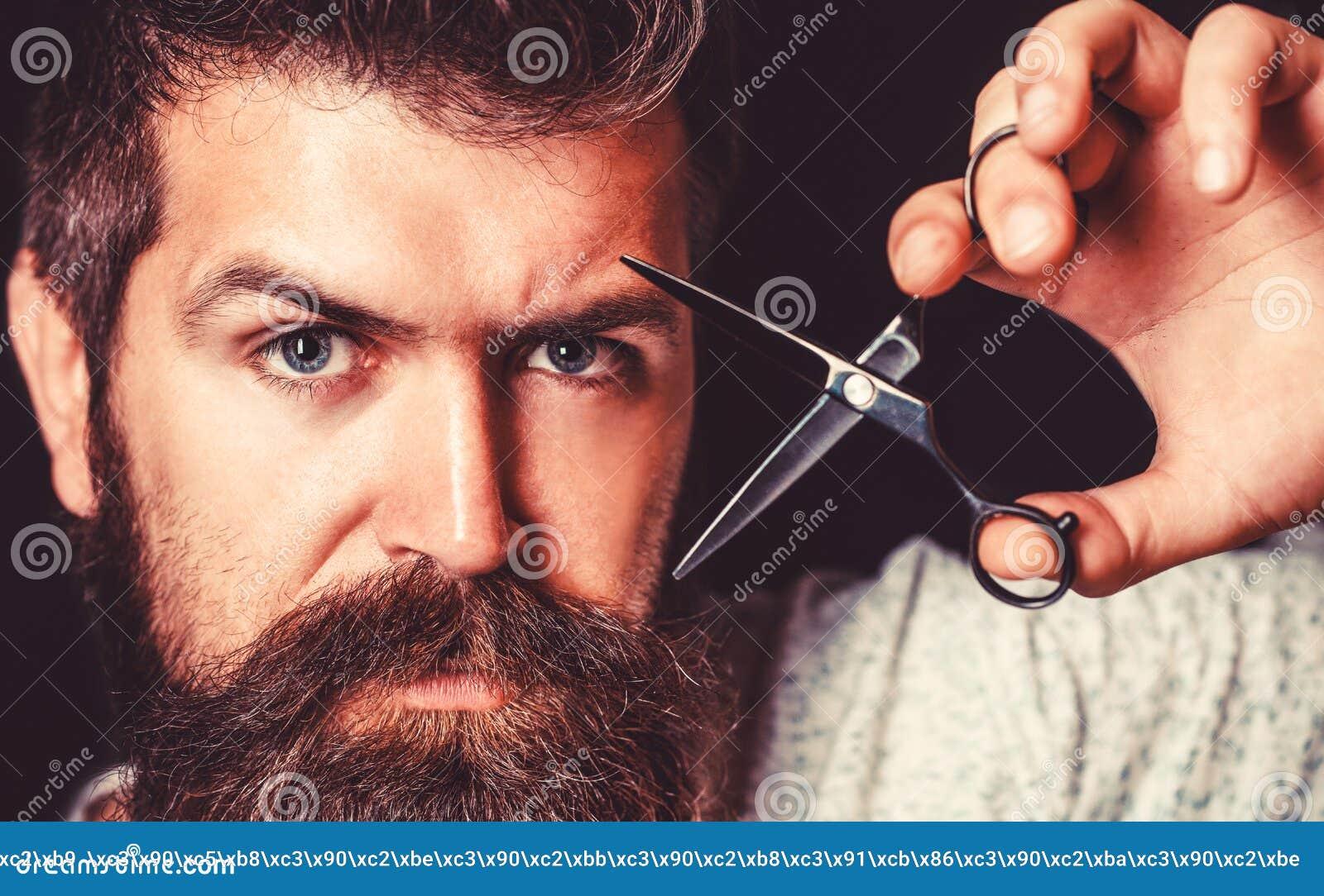 供以人员在理发店的理发 理发师剪刀,理发店 残酷男性,有髭的行家 男性在理发店