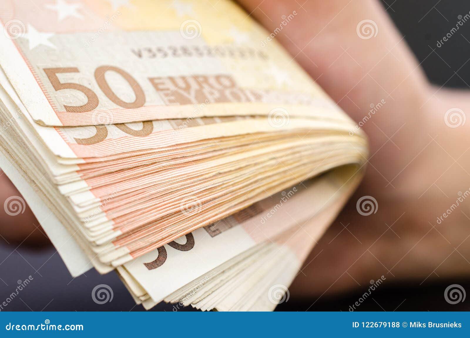 供以人员拿着几50张欧洲钞票的手