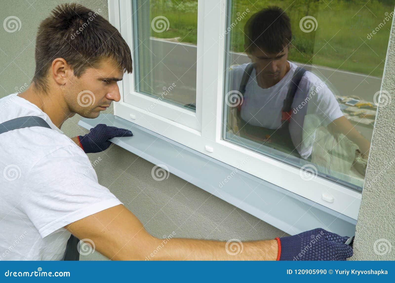 供以人员测量外在框架和PVC窗口金属基石大小的防护手套的工作者