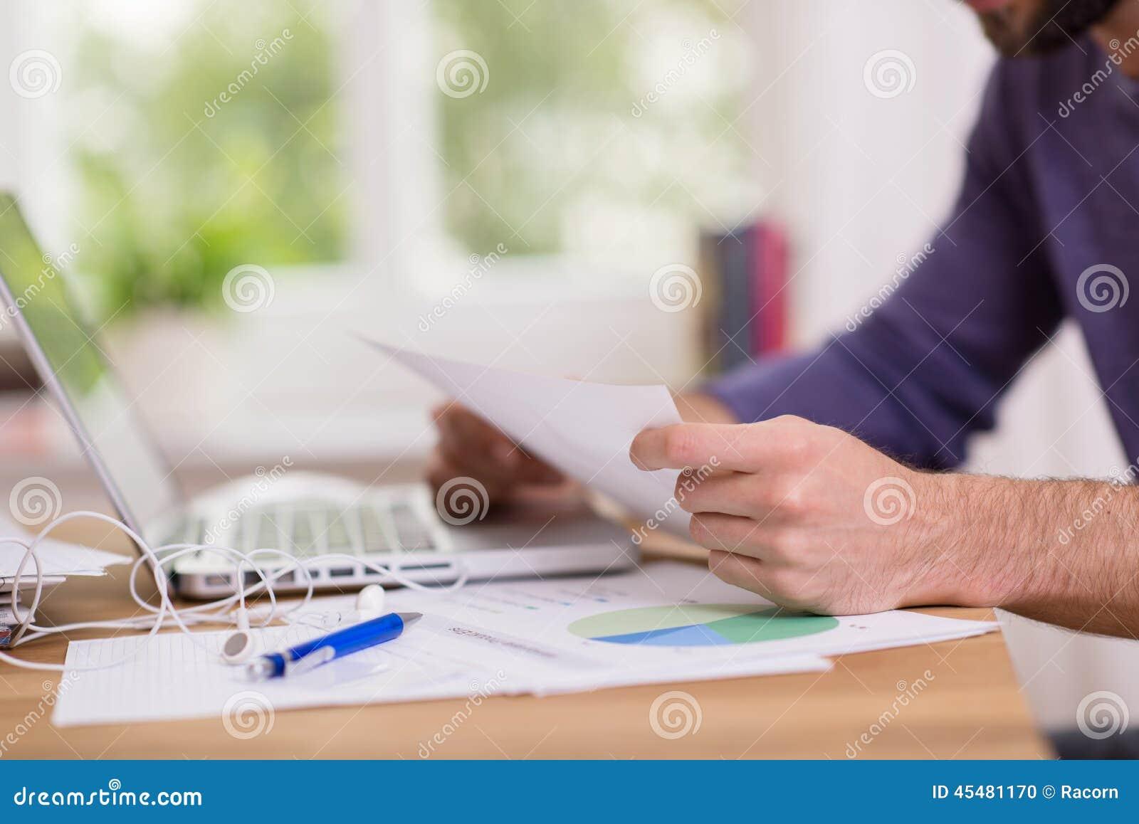 供以人员坐的工作在他的读文件的书桌