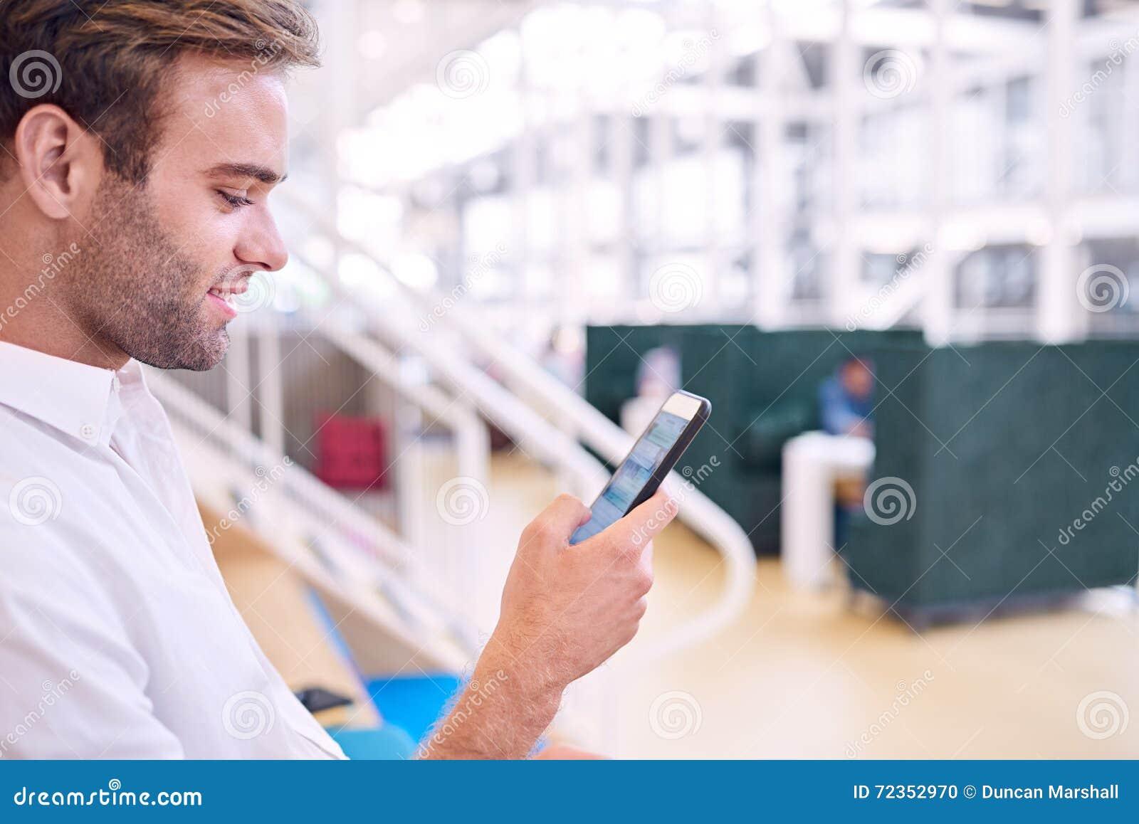 供以人员微笑,当在他新的现代智能手机时的传讯