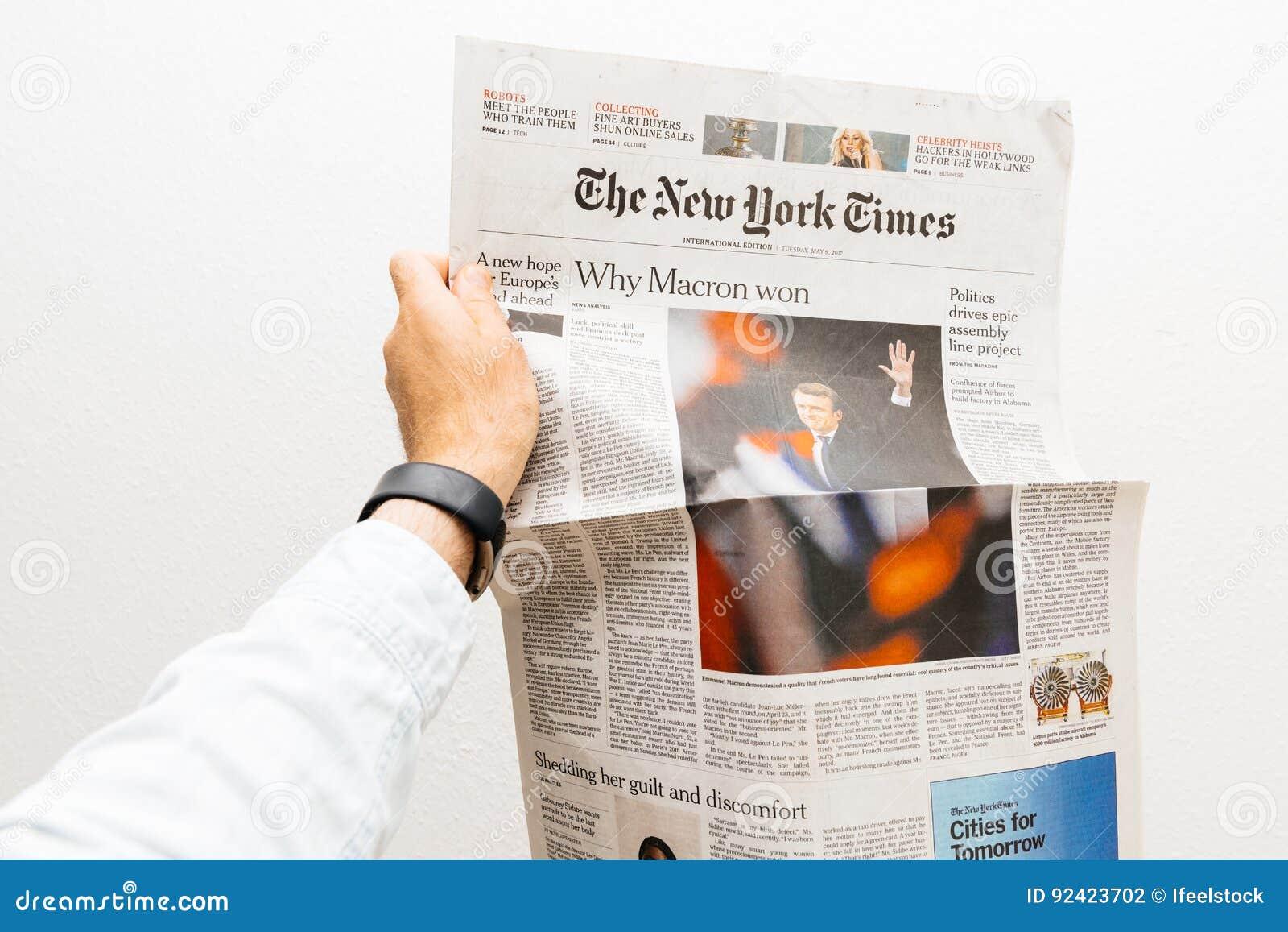 供以人员拿着与伊曼纽尔Macron的纽约时报报纸