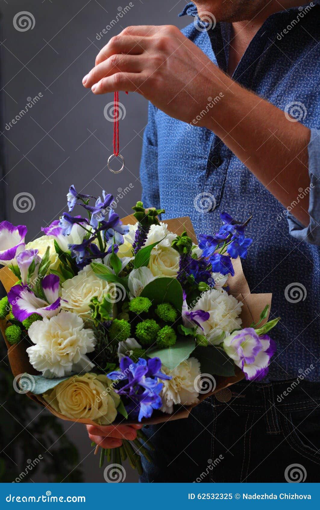 供以人员掩藏定婚戒指在花束