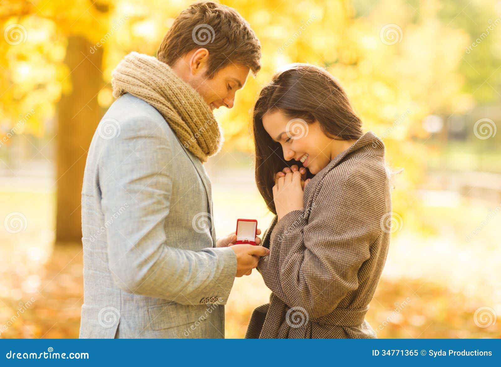 供以人员提议给一名妇女在秋天公园