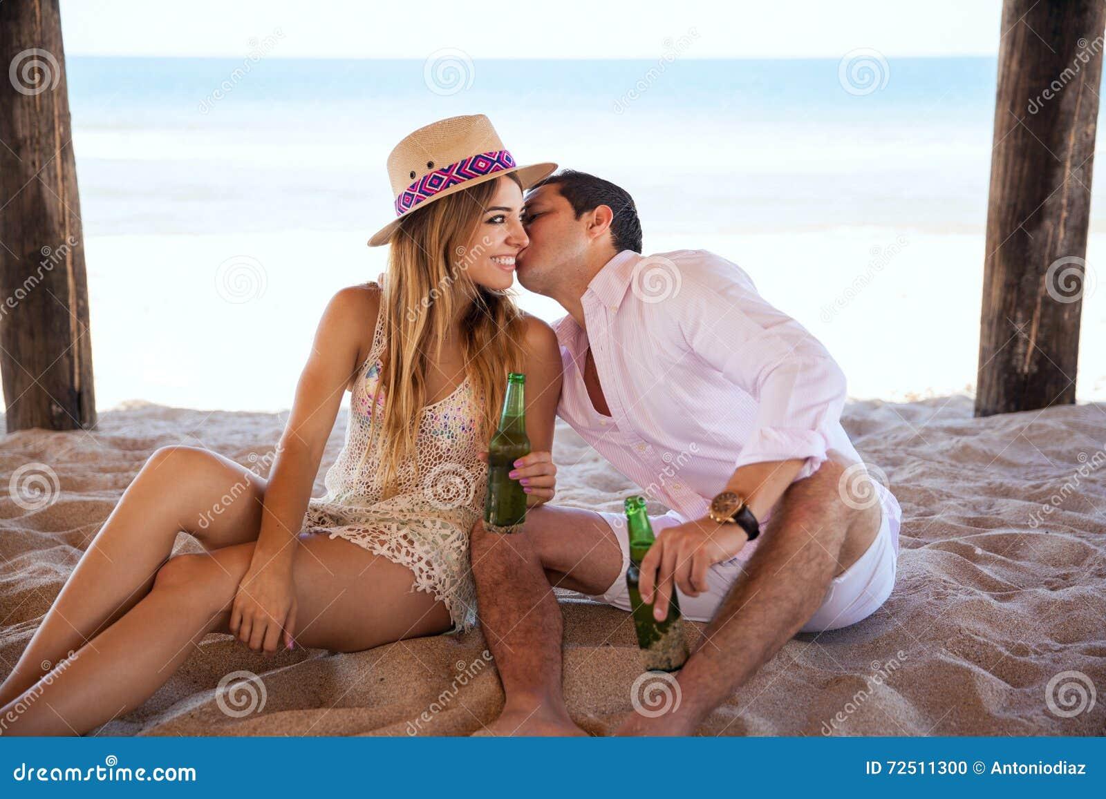供以人员耳语在女朋友的耳朵在海滩