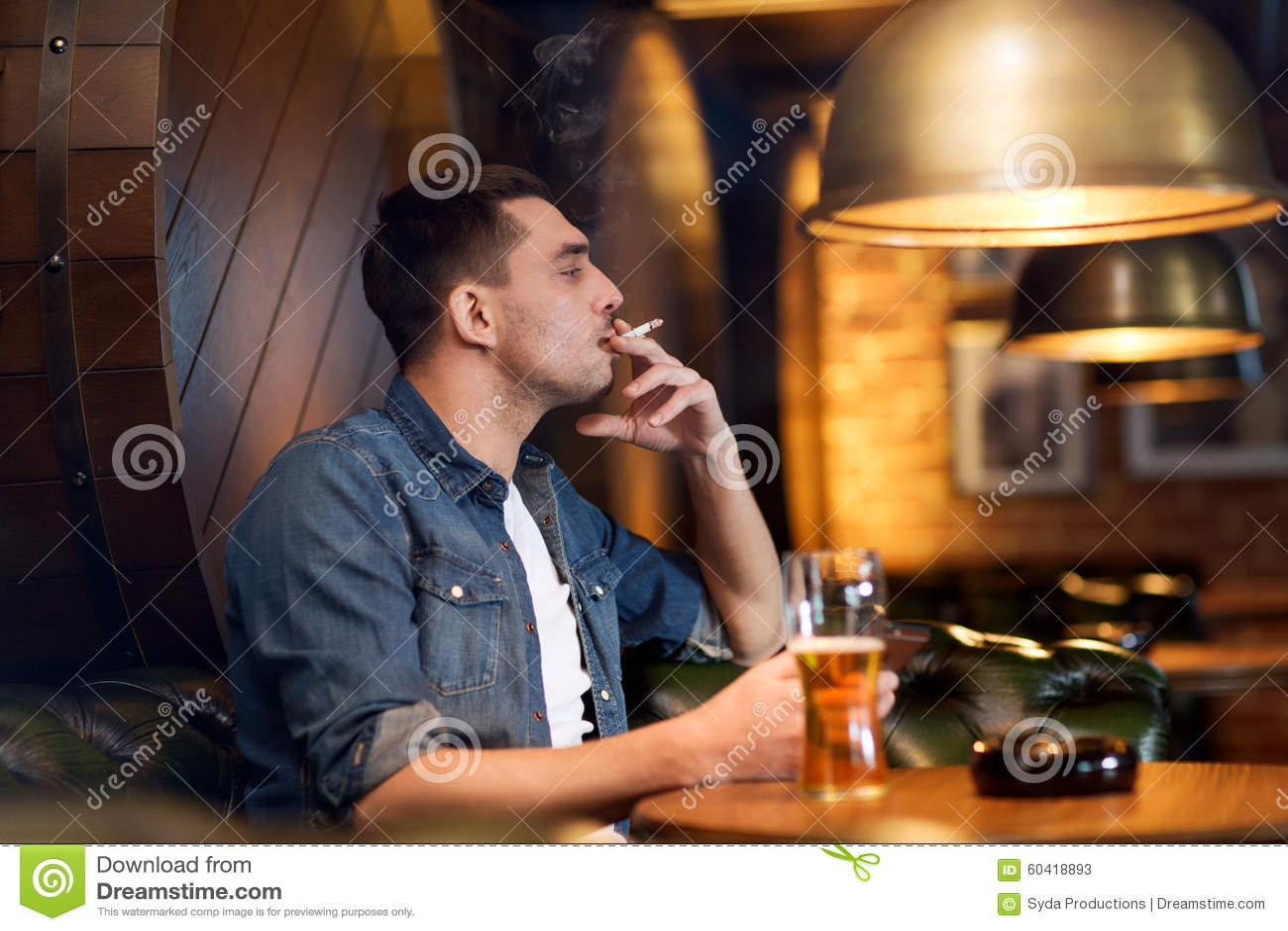 供以人员饮用的啤酒和抽烟的香烟在酒吧