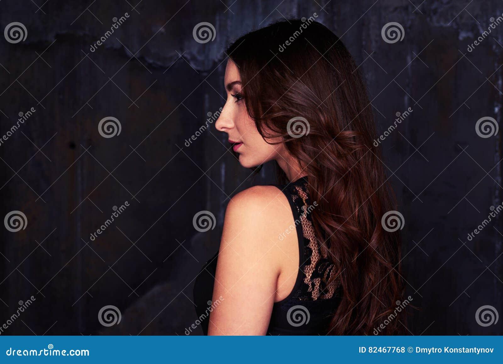 侧视图令人愉快女性佩带的鞋带黑色礼服看