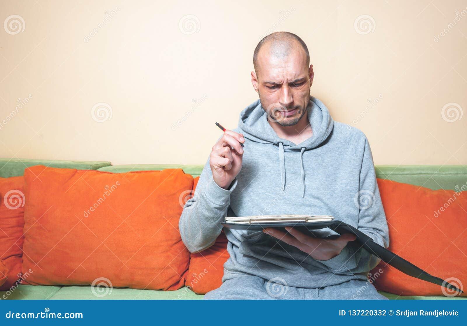 便服的年轻秃头人有设法滑稽和迷茫的表情的计算他的与笔和pape的年税款债务