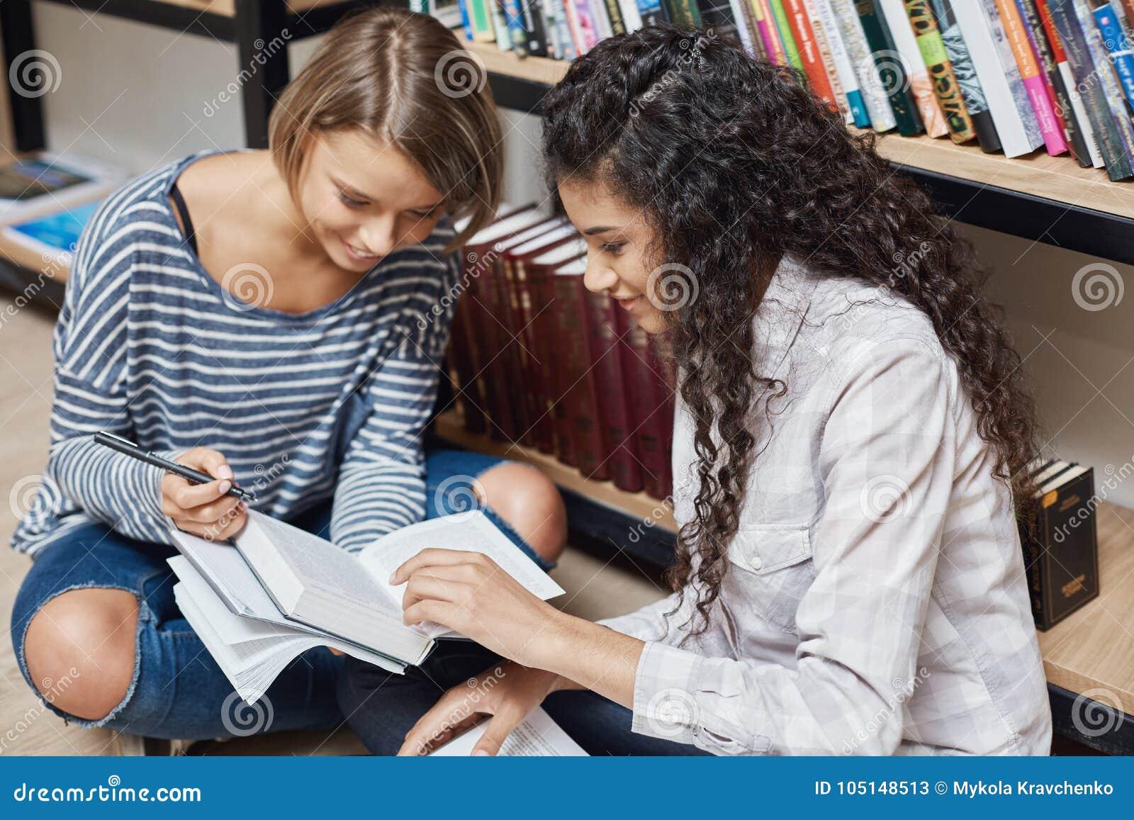 便衣的两名更加成功的女性多种族学生坐地板在大学图书馆里,为做准备