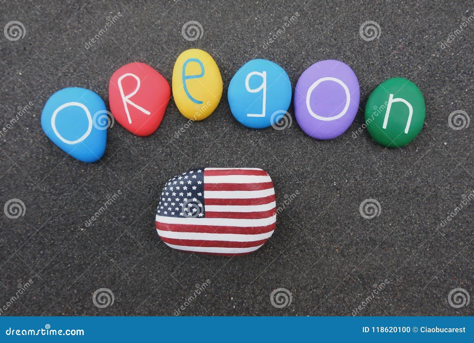 俄勒冈、美利坚合众国、纪念品与色的石头和美国旗子在黑火山的沙子