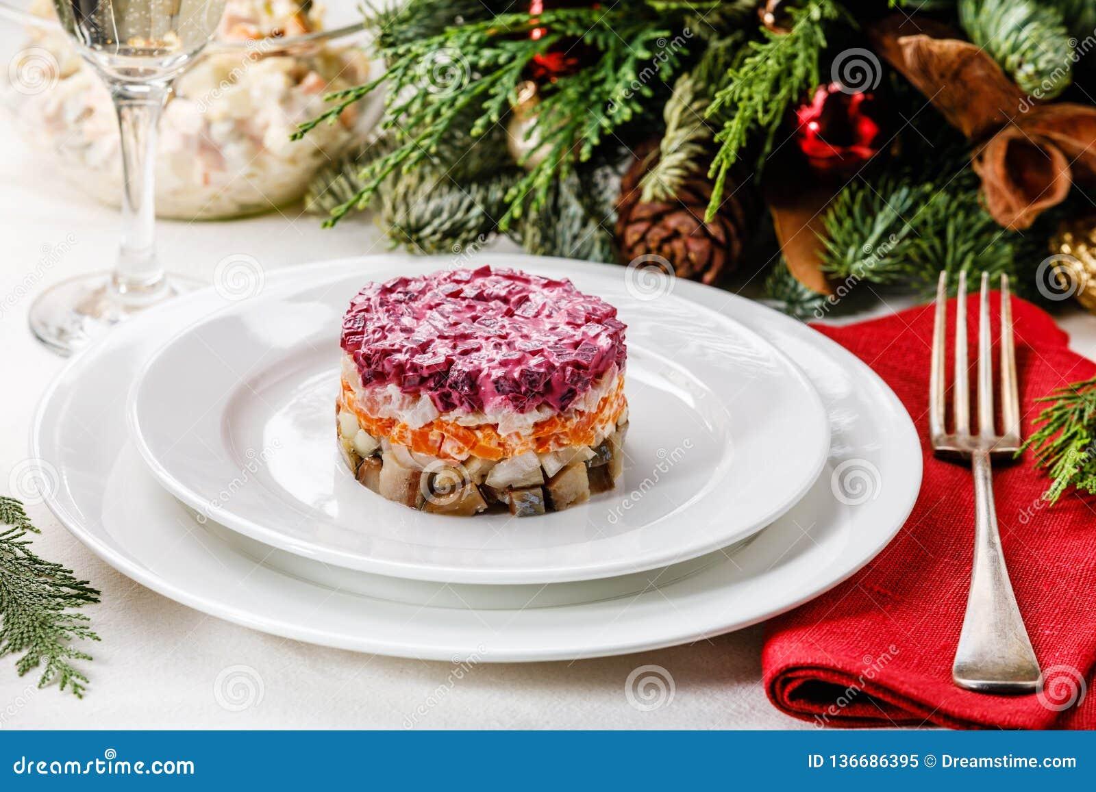 俄国假日分层了堆积沙拉用鲱鱼、甜菜、红萝卜、葱、土豆和鸡蛋