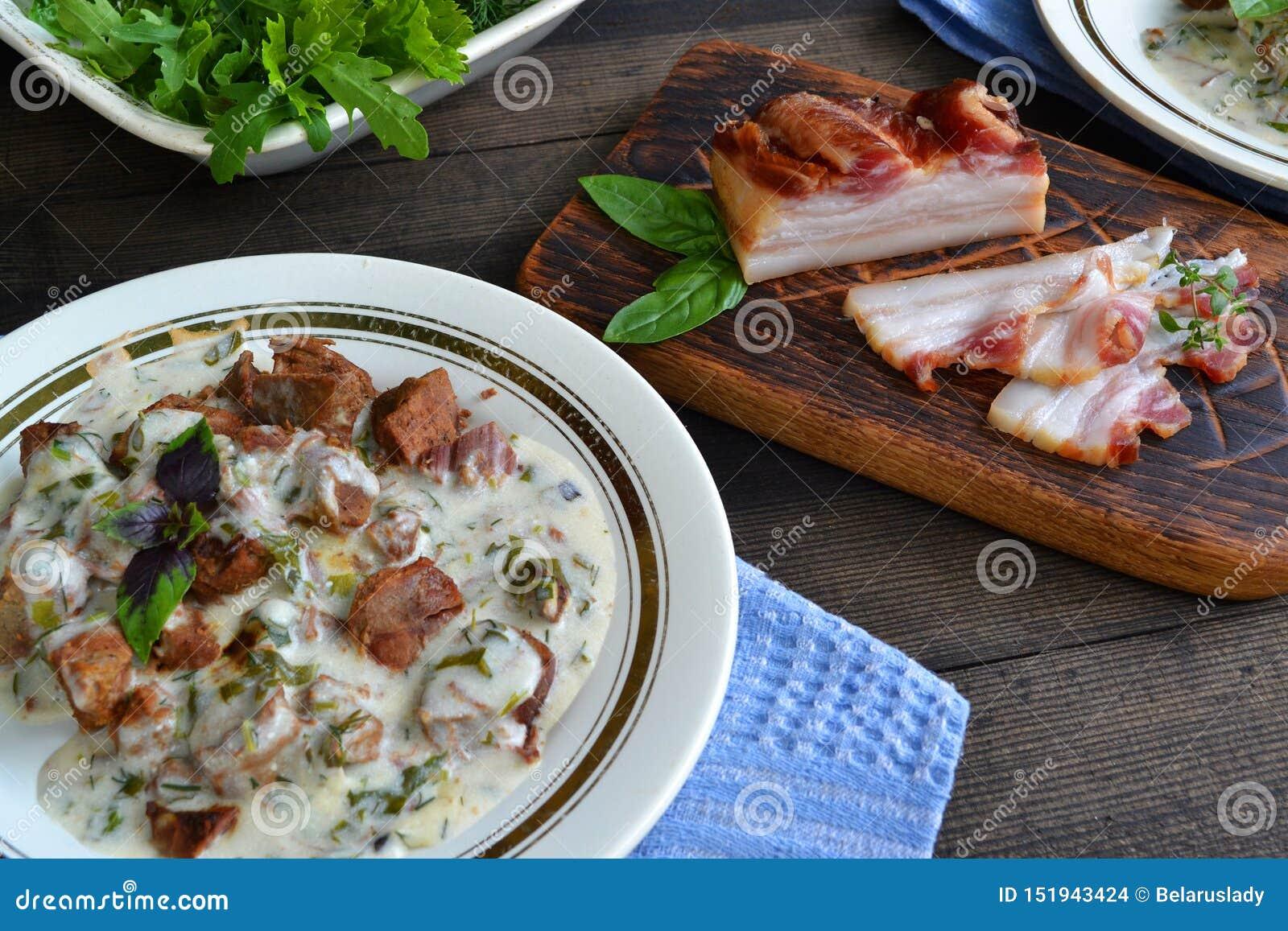 俄国烹调:特写镜头牛肉肉炖与在陶瓷罐的菜在木背景