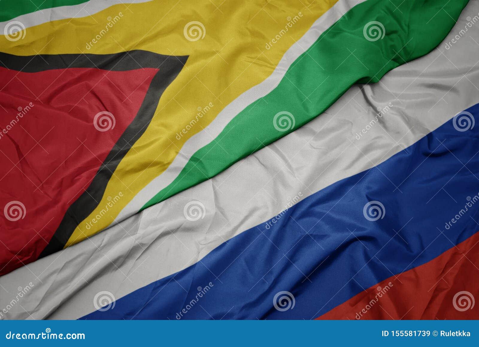 俄罗斯的挥动的五颜六色的旗子和圭亚那的国旗