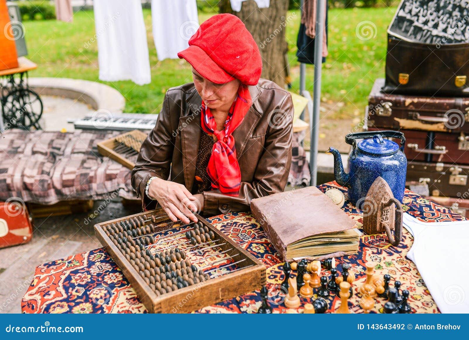 俄罗斯,城市莫斯科- 2014年9月6日:有皮夹克和一顶红色贝雷帽的一名妇女依靠一个计数的委员会 计数委员会
