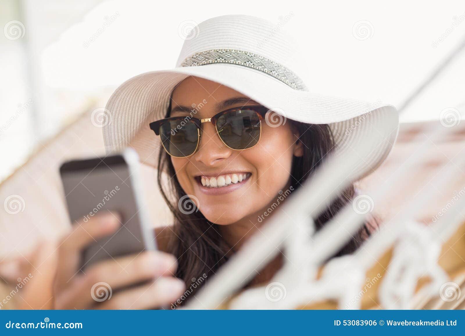 俏丽深色放松在吊床和发短信与她的手机