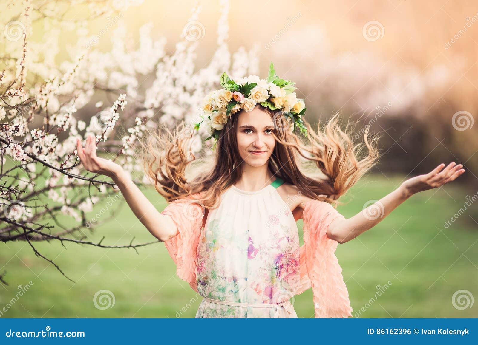 俏丽的女孩在春天开花庭院里