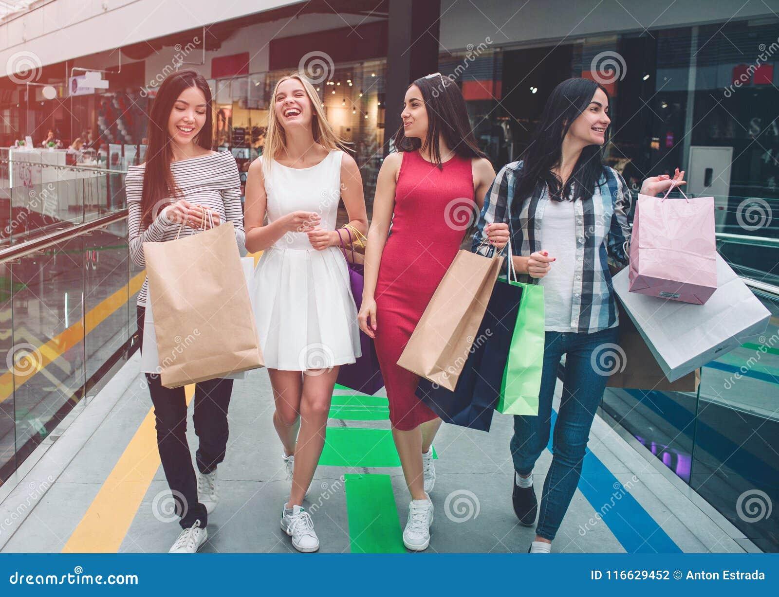 俏丽的女孩在购物中心一起走 他们购物 少妇有袋子在他们的手 女孩笑