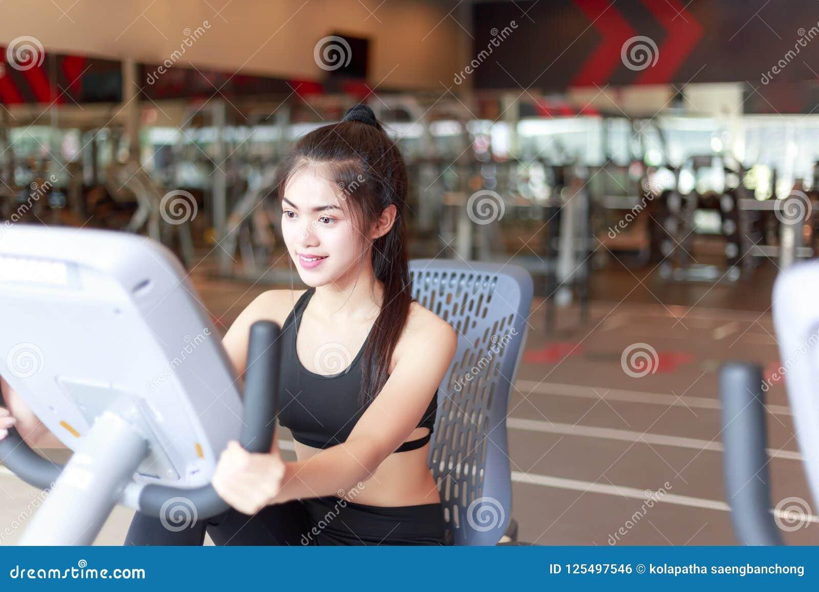 俏丽的女孩循环自行车机器在体育健身房 charmin