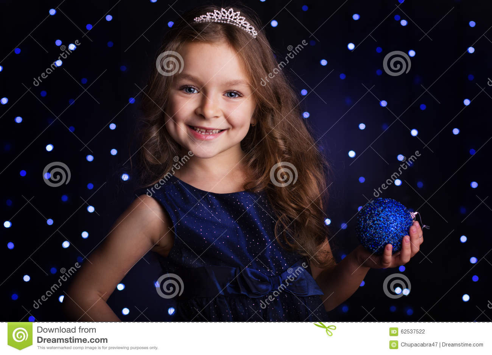 俏丽的女孩拿着蓝色圣诞节球