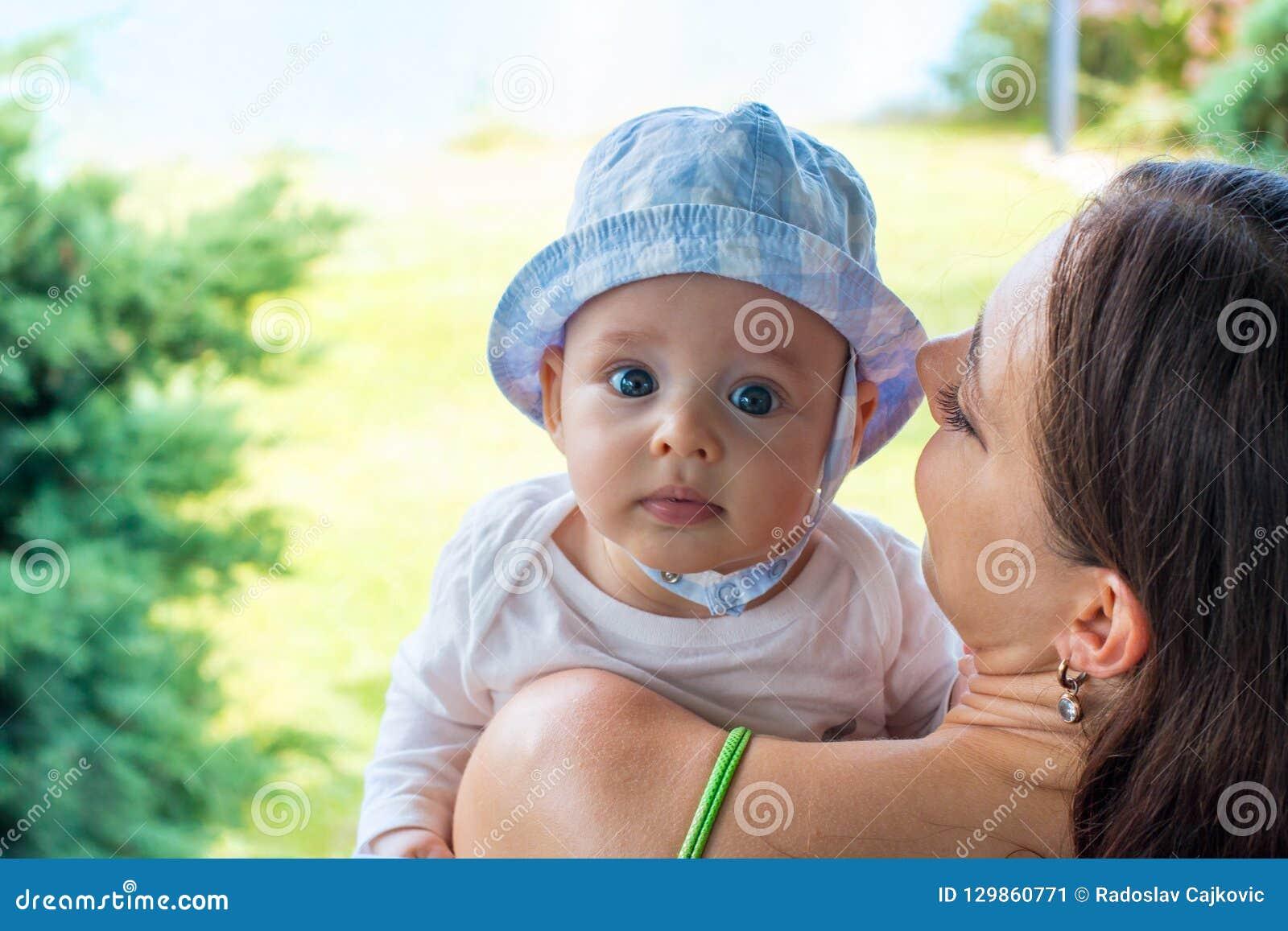 俏丽的帽子的,婴儿面孔画象母亲拥抱逗人喜爱的蓝眼睛的婴孩
