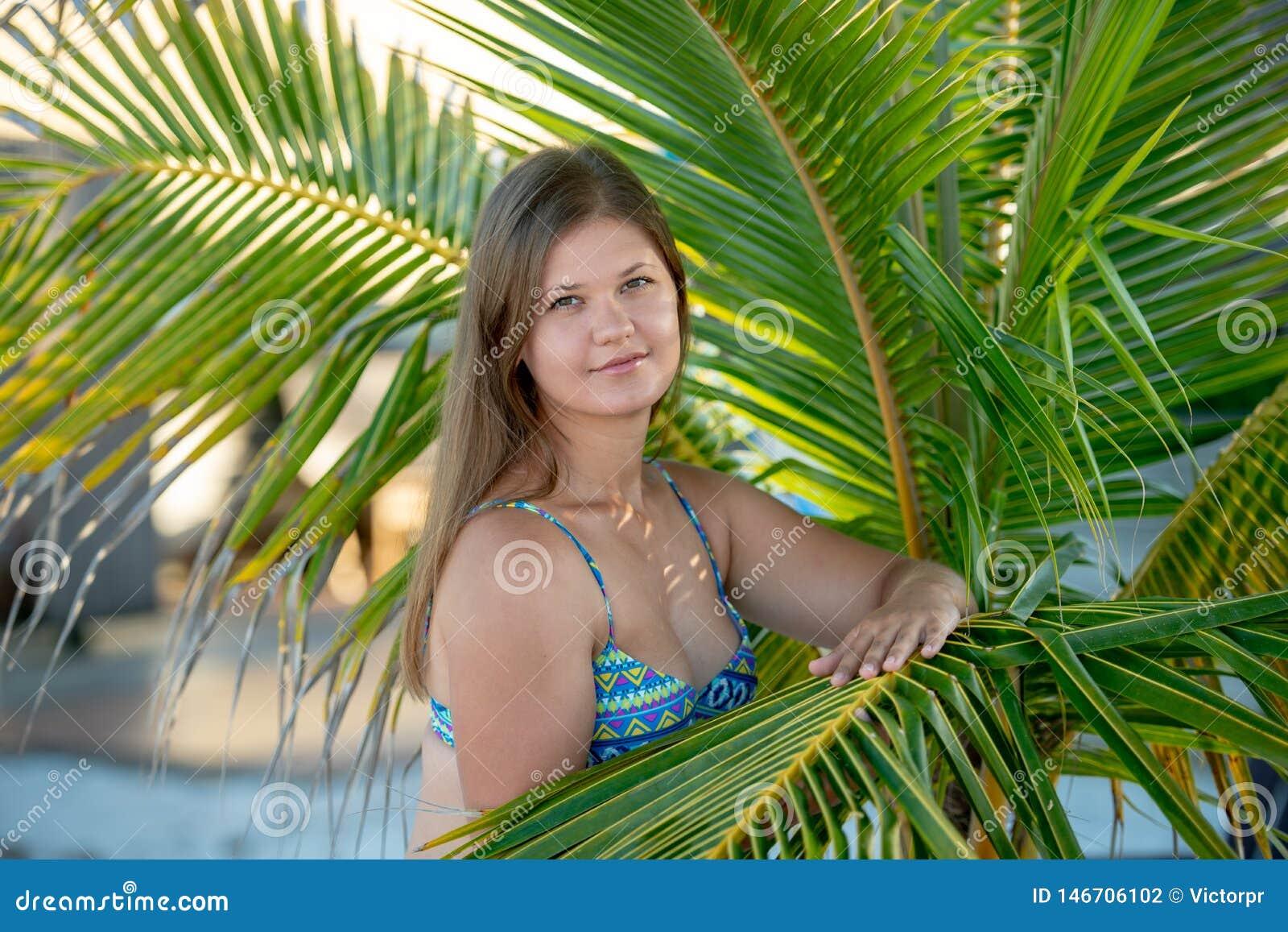 俏丽的年轻女人在棕榈树下