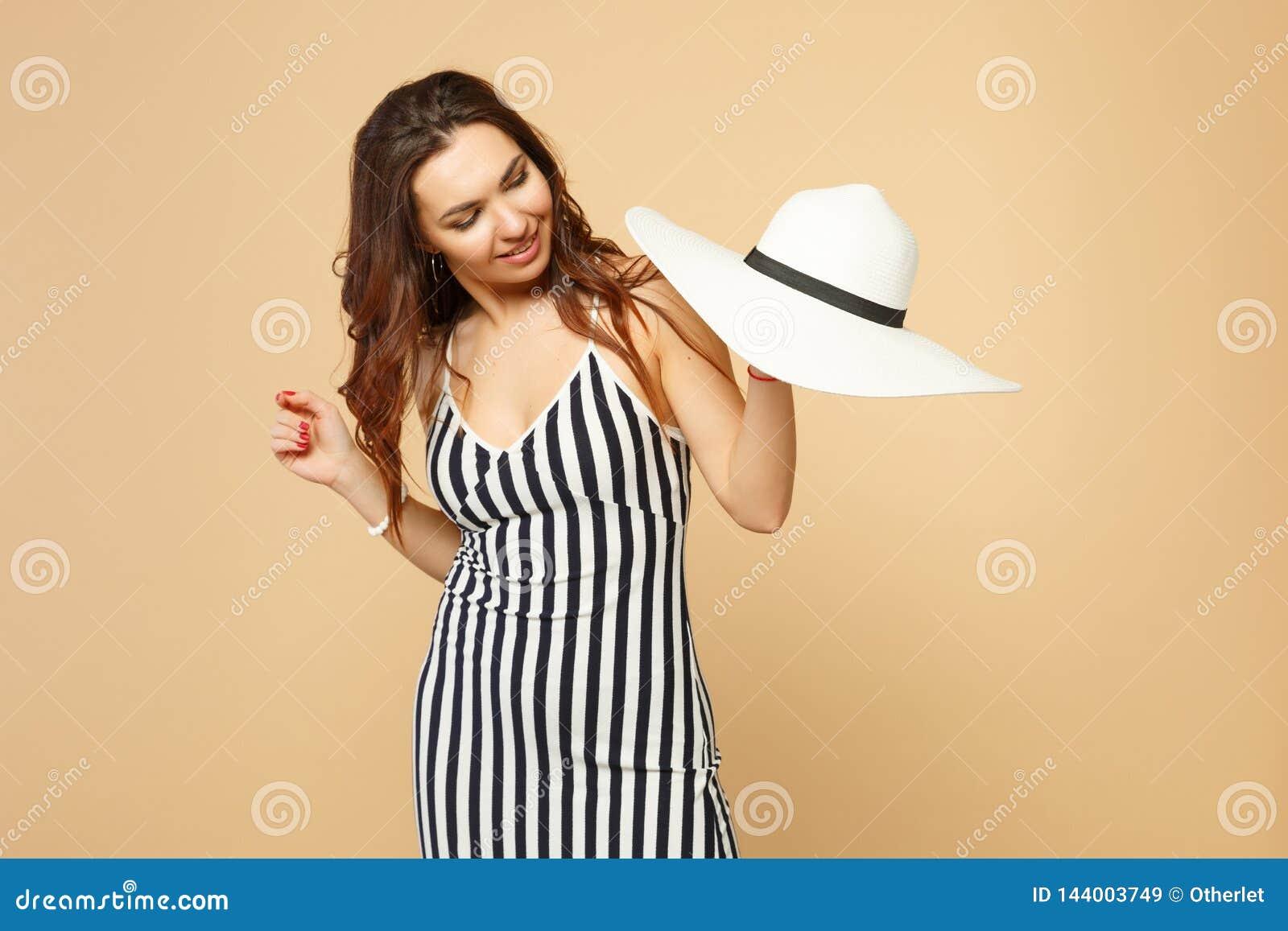 俏丽的年轻女人画象在手中举行黑白镶边的礼服的,看在淡色灰棕色隔绝的帽子