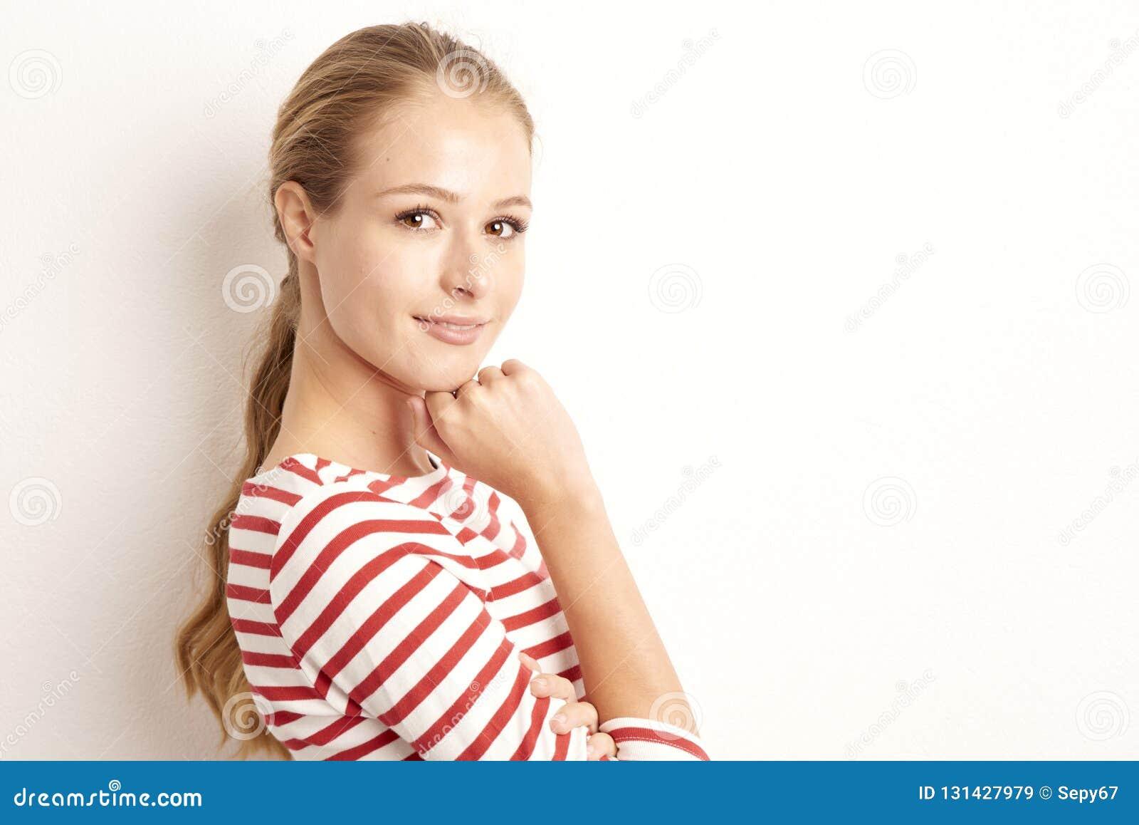 俏丽的年轻女人lookig演播室画象在照相机和微笑的,当站立对被隔绝的白色背景和使用与时