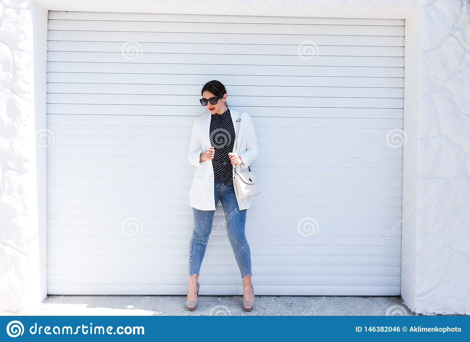 俏丽的年轻摆在白色墙壁背景的时尚肉欲的妇女穿戴在样式牛仔裤成套装备和白色夹克