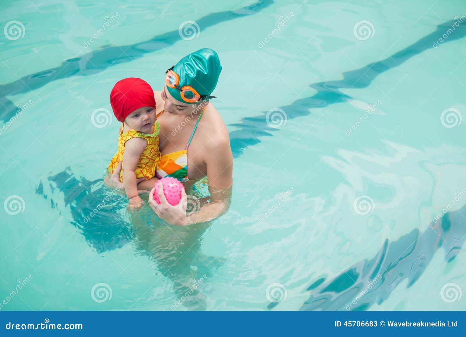 俏丽的母亲和婴孩游泳池的