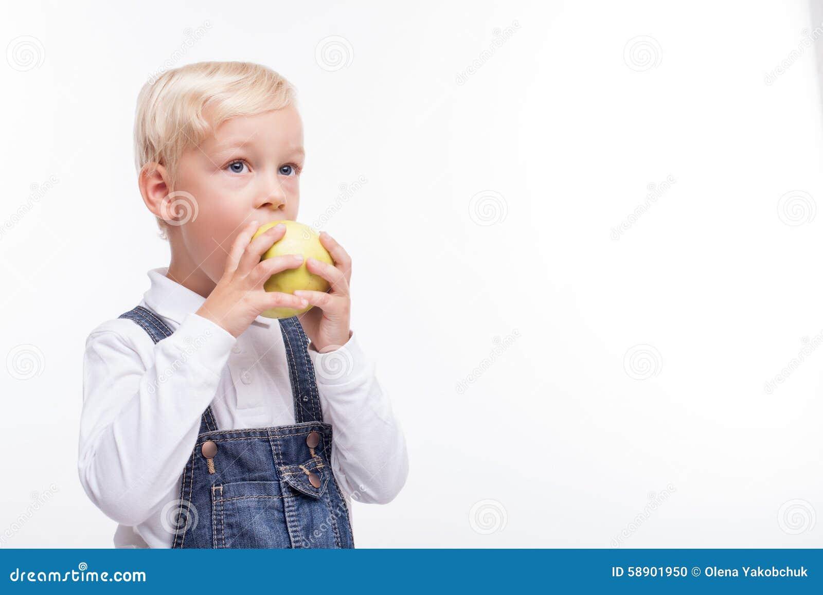 俏丽的男孩吃绿色果子