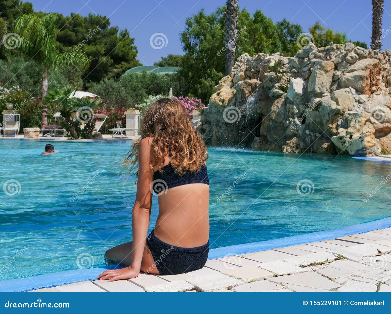 俏丽的运动晒黑女孩在游泳场坐假期