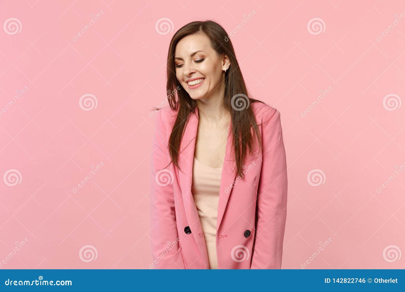 保持眼睛的有吸引力的俏丽的笑的年轻女人佩带的夹克画象闭上隔绝在粉红彩笔墙壁上