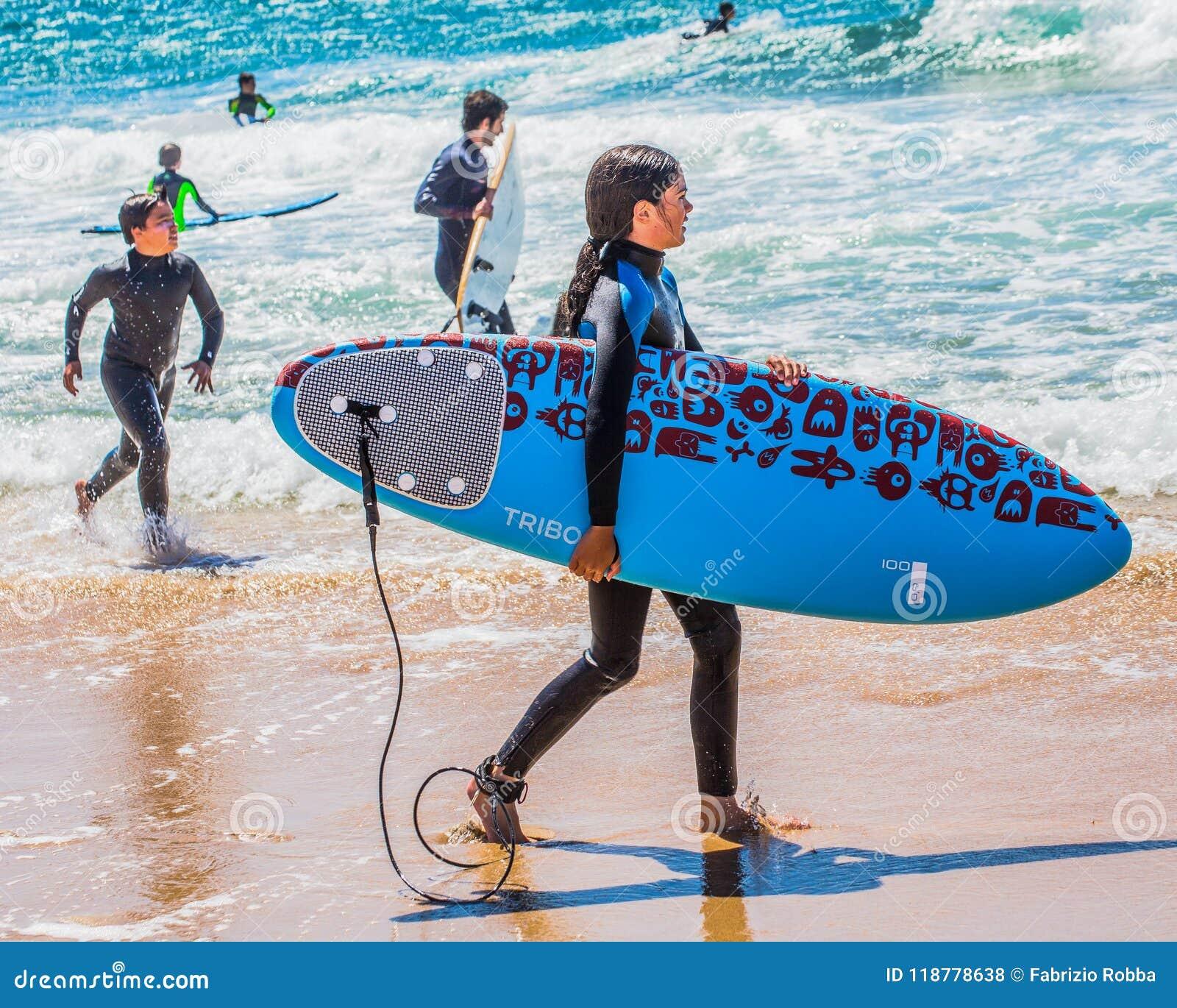 保温潜水服的女孩有一个冲浪板的在海滩的一个晴天