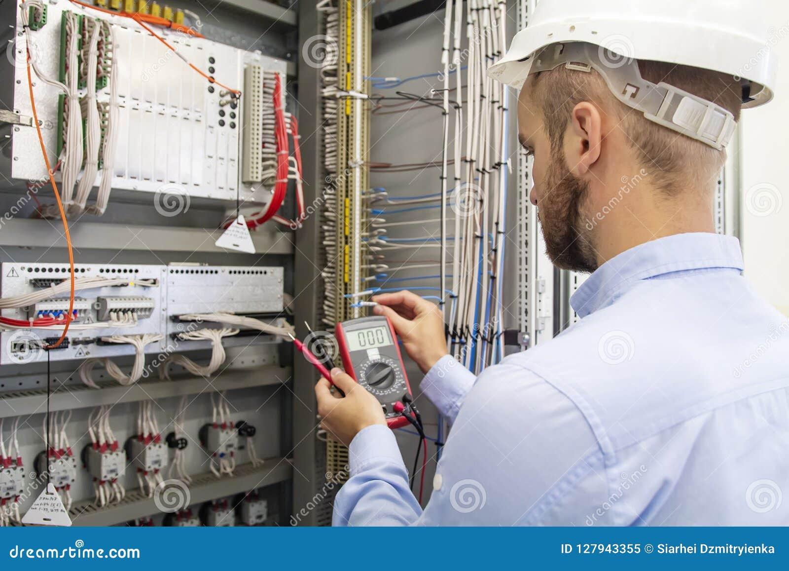 保险丝箱子的电工技术员 控制板的维护工程师 工作者测试自动化设备