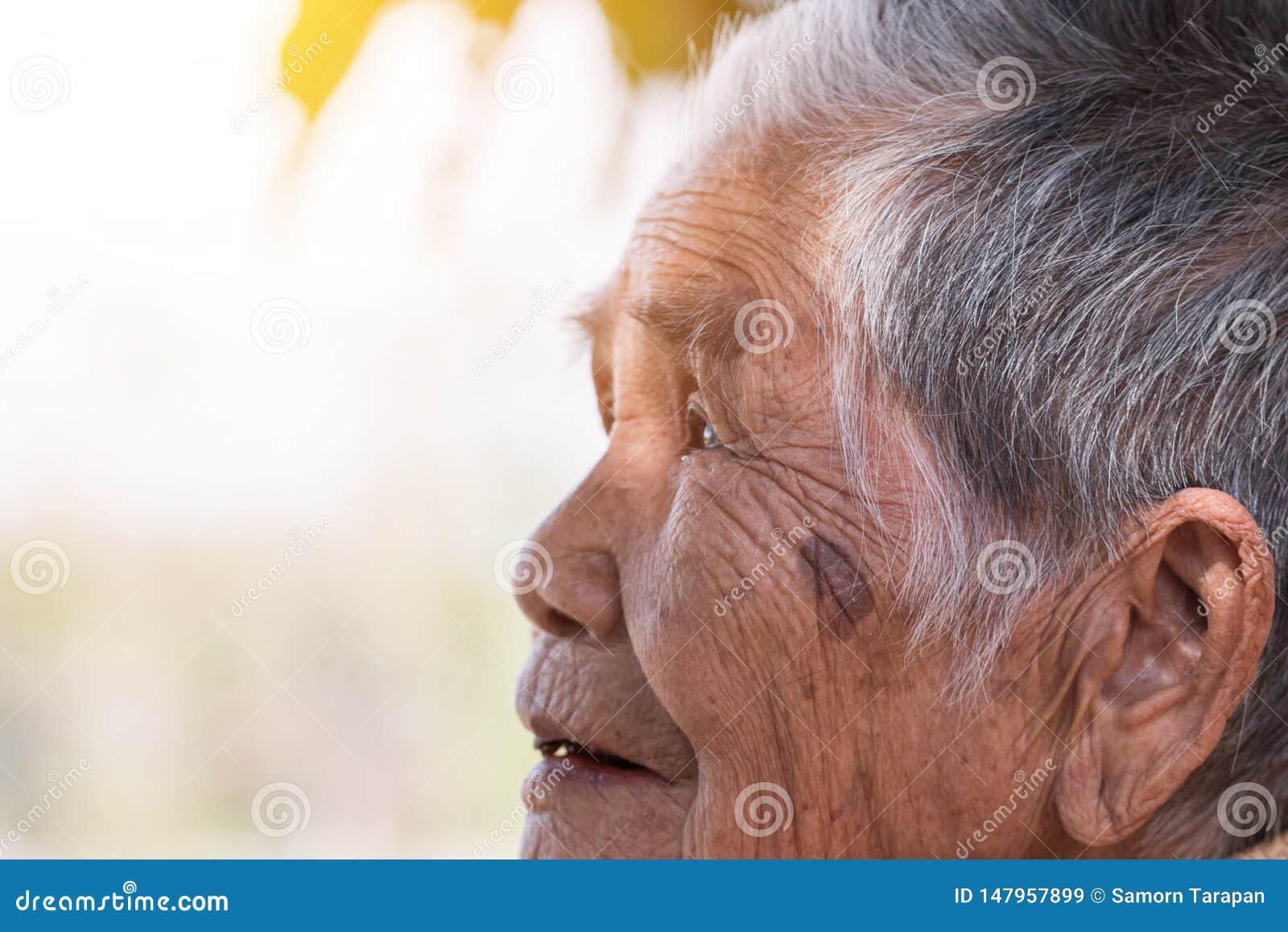 保险概念的老人:单独坐与她的黑牙的亚裔老妇人画象在室外在好日子