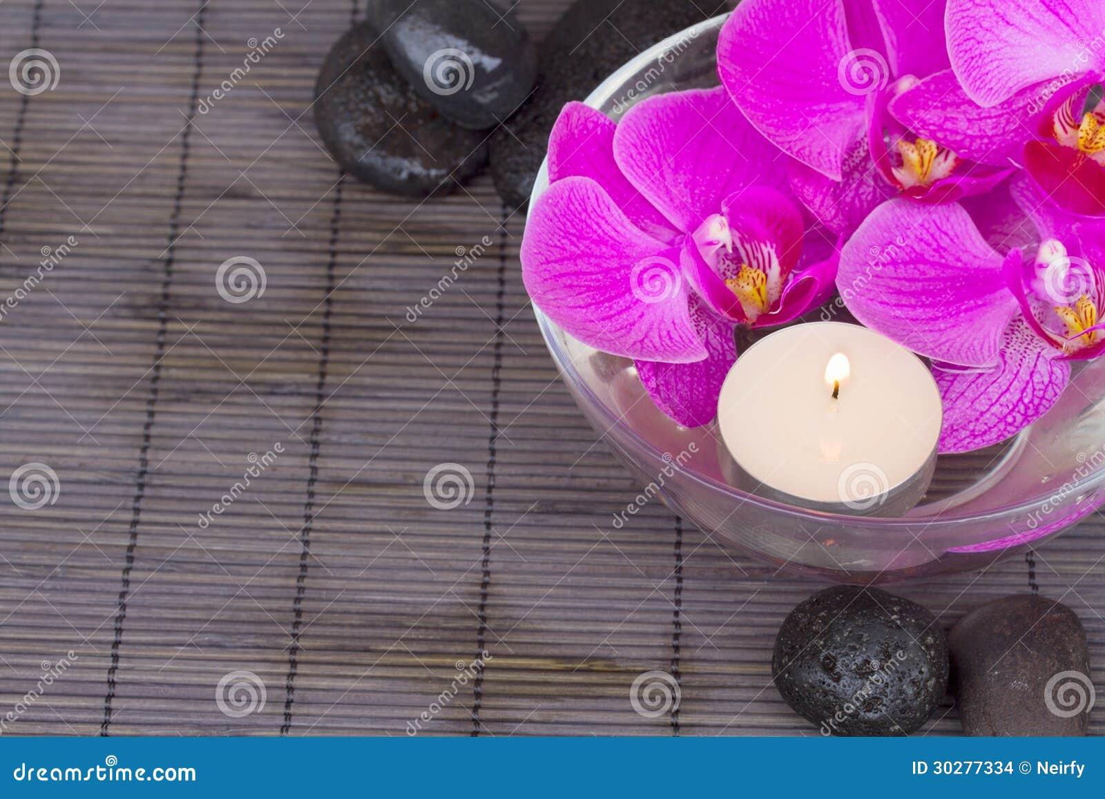 与蜡烛和按摩石头的兰花