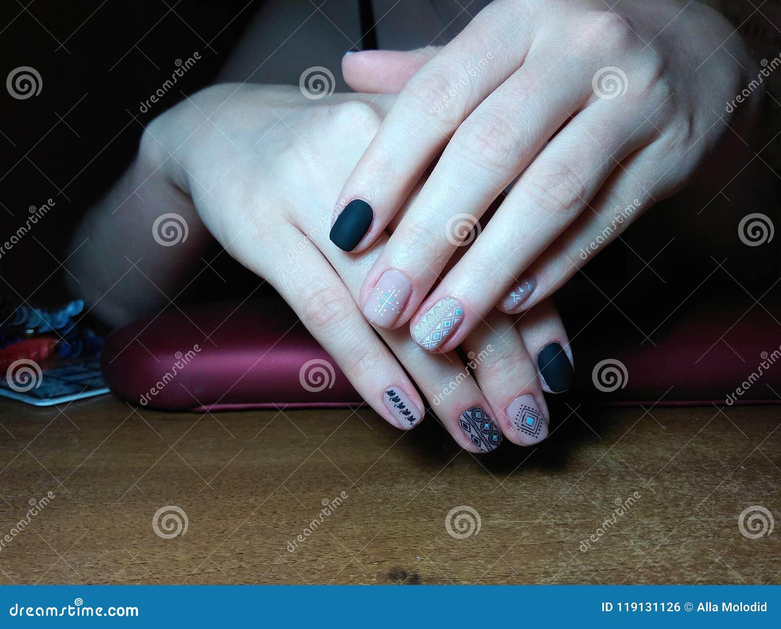 修指甲师在她的手优秀地做了她的工作与一个波兰胶凝体的美好的修指甲,并且客户是愉快的