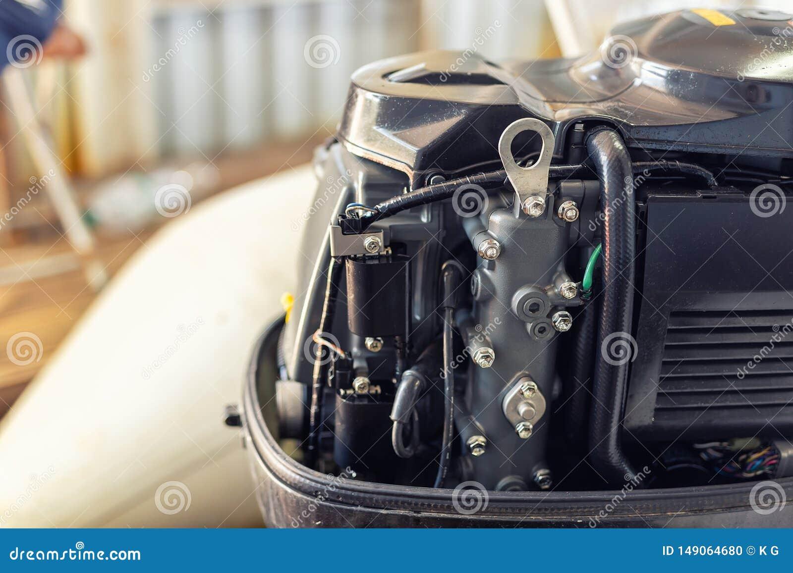 修理在小船车库的可膨胀的汽艇引擎 船引擎季节性服务和维护 有开放盖子的船马达