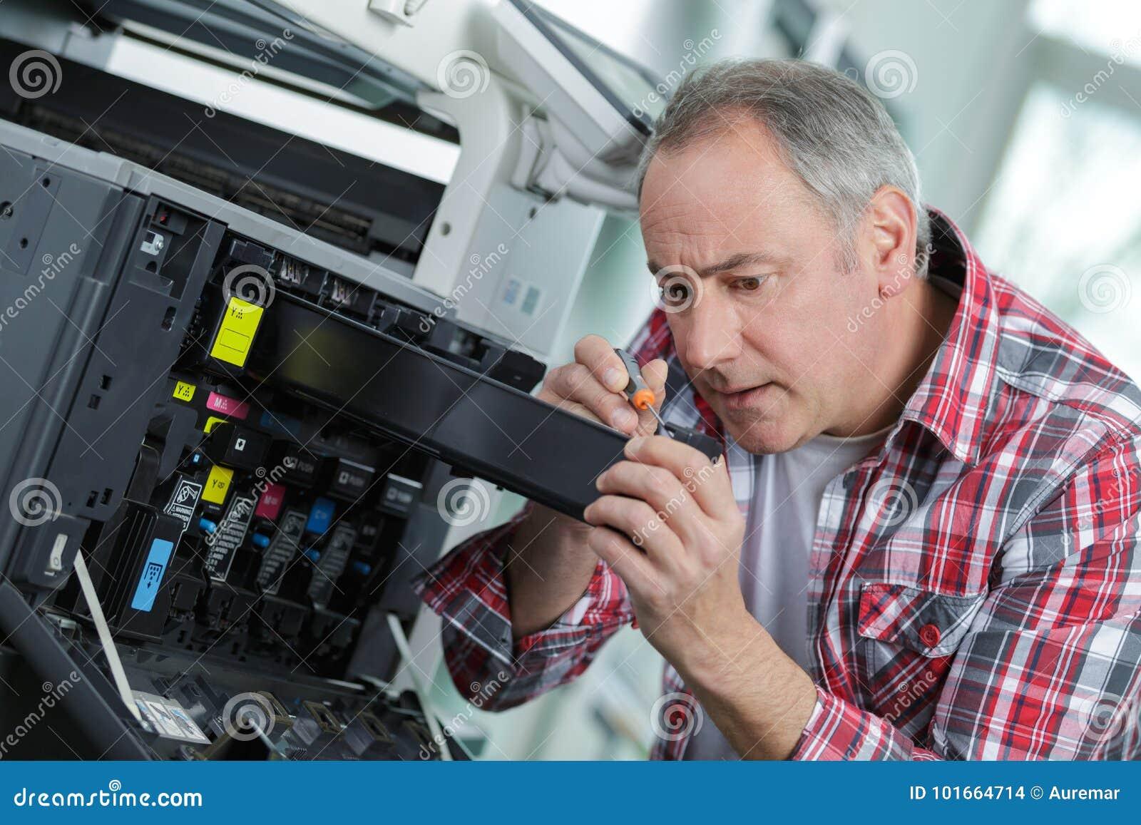 修理大影印机调色剂的老人和技术员