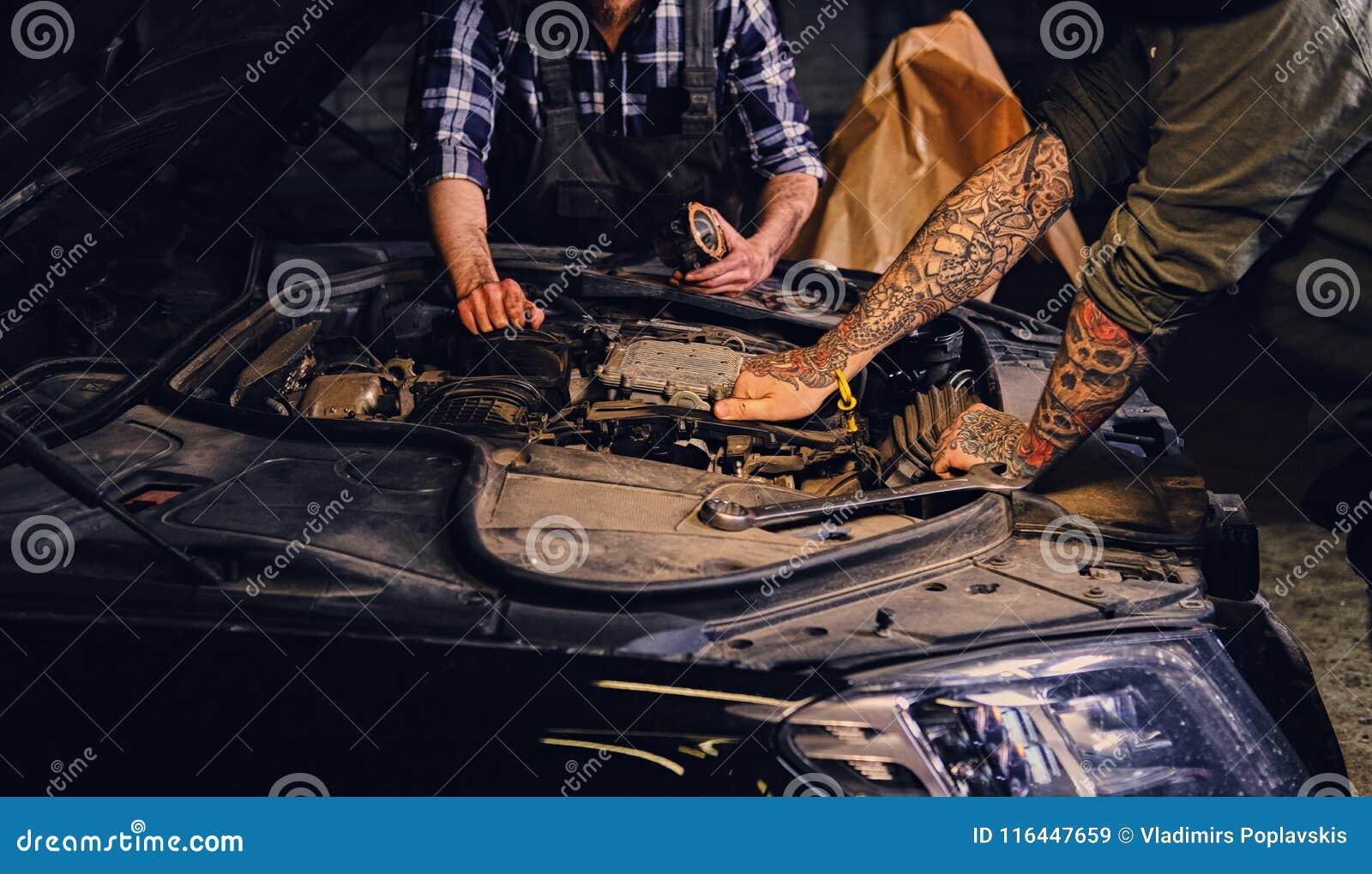 comp 关闭两位技工的图象有纹身花刺的在胳膊,修理汽车` s发动机零件